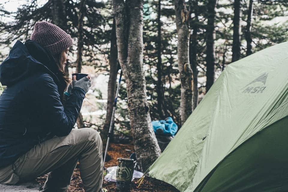 Woman sitting next to her tent